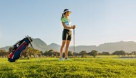 Żeński golfista czeka trójnik daleko na polu golfowym obrazy royalty free