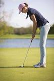 Żeński golfowego gracza kładzenie na zieleni Fotografia Stock