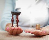 Żeński hand& -39; s z hourglass i monetą zdjęcie royalty free