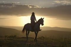 Żeński horseback jeździec i końska przejażdżka przegapiać przy Lewa przyrody Conservancy w Północnym Kenja, Afryka przy zmierzche Obraz Royalty Free