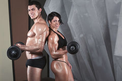 Żeński i męski bodybuilder Stać nad ciemnym tłem Fotografia Stock