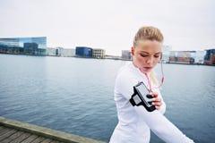 Żeński jogger monitoruje jej postęp na smartphone zdjęcia royalty free