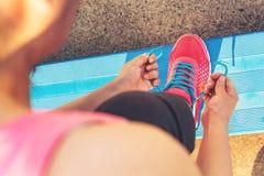 Żeński jogger wiąże jej buty na blicharzach fotografia stock