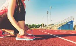 Żeński jogger wiąże jej buty na stadium śladzie obraz royalty free