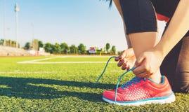 Żeński jogger wiąże jej buty na stadium polu zdjęcie royalty free