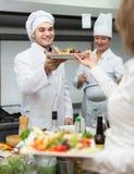 Żeński kelner bierze naczynie przy kuchnią Fotografia Stock