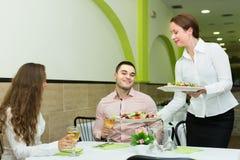 Żeński kelner porci gości stół Zdjęcie Royalty Free