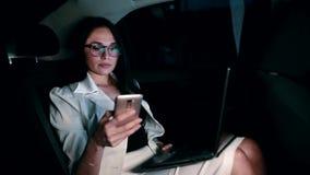 Żeński kierownik texting przy telefonem komórkowym w tylnym siedzeniu poruszający samochód zdjęcie wideo