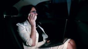 Żeński kierownik texting przy telefonem komórkowym w tylnym siedzeniu poruszający samochód zbiory wideo