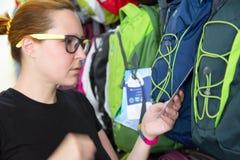 Żeński klient wybiera plecaka przy Detalicznym sklepem zdjęcia royalty free