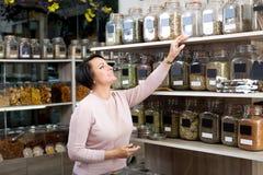 Żeński klient wybiera różnorodnych ziele zdjęcie royalty free