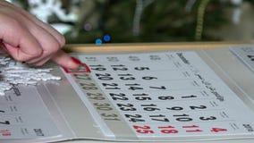 Żeński kobieta palca dosunięcia papieru kalendarza markier przez ostatnich dni rok zbiory