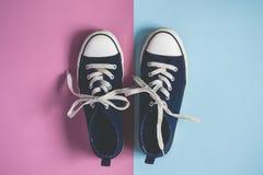 Żeński lub męski zmrok - błękitni Sneakers na różowym błękitnym pastelowym tle Zdjęcie Royalty Free