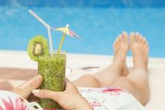 Żeński lying on the beach na sunbed i mienie szkło świeży kiwi smoothie Obraz Stock