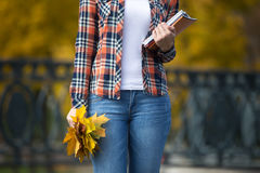 Żeński młody uczeń outdoors trzyma kolorów żółtych liście Obrazy Stock
