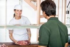 Żeński masarki sprzedawania mięso klient Fotografia Stock
