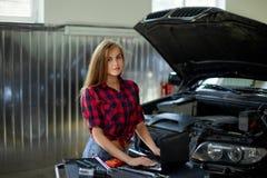 Żeński mechanik w sprawdzać koszula przy pracą auto stacja obsługi Fotografia Stock