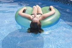 Żeński nastolatek unosi się na pławiku w basenie Obraz Royalty Free