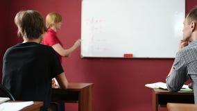 Żeński nauczyciel daje wykładowi przy uniwersytetem transmituje notatnika zbiory