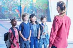 Żeński nauczyciel wyjaśnia multirace ucznie w boisku szkolnym obraz royalty free