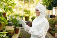 Żeński naukowiec jest ubranym czystego kostiumu writing w schowku Obraz Stock