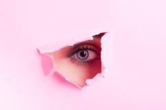 Żeński oko z makijażem patrzeje przez cięcie kartonu out Zdjęcia Royalty Free