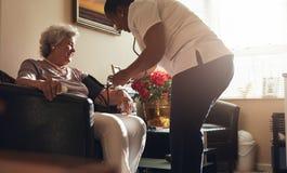 Żeński opieka zdrowotna pracownik bierze ciśnienie krwi starszy pacjent obraz stock