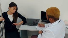 Żeński pacjent opowiada z samiec lekarki plombowaniem w medycznej formie na szczudłach zbiory