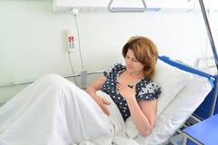 Żeński pacjent Z szczerym bólowym lying on the beach na łóżku w szpitalnym oddziale Fotografia Royalty Free
