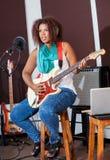 Żeński piosenkarz Bawić się gitarę Podczas gdy Siedzący Na stolec Zdjęcia Stock