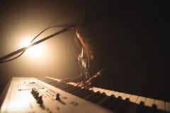 Żeński piosenkarz bawić się pianino podczas gdy wykonujący w muzyka koncercie Fotografia Stock