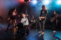 Żeński piosenkarz z mikrofonem i rock and roll zespołem bawić się hard rock muzykę Obrazy Royalty Free
