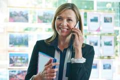 Żeński pośrednik w handlu nieruchomościami Na telefonie W biurze Zdjęcia Stock