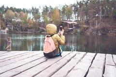 Żeński podróżnik siedzi na drewnianym molu blisko pięknego jeziora w sosnowych lasowych i biorą fotografiach na telefonie komórko Obraz Royalty Free