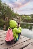 Żeński podróżnik siedzi na drewnianym molu blisko pięknego jeziora w sosnowych lasowych i biorą fotografiach na telefonie komórko Fotografia Royalty Free