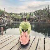 Żeński podróżnik siedzi na drewnianym molu blisko pięknego jeziora w sosnowych lasowych i biorą fotografiach na telefonie komórko Fotografia Stock