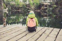 Żeński podróżnik siedzi na drewnianym molu blisko pięknego jeziora w sosnowym lesie Zdjęcia Royalty Free