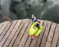 Żeński podróżnik siedzi na drewnianym molu blisko pięknego jeziora w sosnowym lesie Obrazy Royalty Free