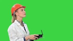 Żeński pracownik budowlany działa żurawia używać pilot do tv na Zielonym ekranie, Chroma klucz zdjęcie wideo