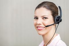 Żeński pracownik Jest ubranym słuchawki Przy centrum telefonicznym Obrazy Royalty Free
