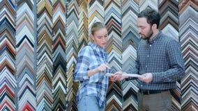 Żeński pracownik opowiada z klientem o obrazek ramy szczegółach w atelier Obraz Royalty Free