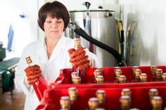 Żeński pracownik sortuje wino butelki Obrazy Royalty Free