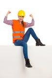 Żeński pracownika budowlanego obsiadanie I Napinać mięśnie fotografia stock