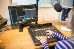 Żeński radiowy gospodarz przed parawanowym operacyjnym rozsądnym melanżerem fotografia stock