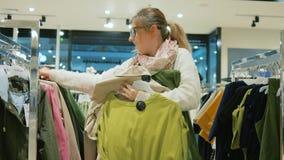 Żeński shopaholic kupuje odzieżowego w sklepie, rozmaitość rzeczy wiesza na wieszakach w odzież sklepie, Kolorowe suknie wewnątrz zbiory