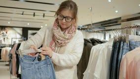 Żeński shopaholic kupuje suknię, cajgi, bluzka, spódnica na sprzedaży, Szalona dziewczyna w zakupy, Modnej i eleganckiej kobiecie zdjęcie wideo