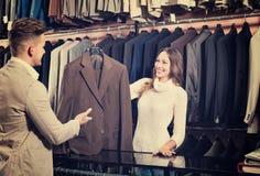 Żeński sklepowego asystenta pomaga klient wybierać kostium zdjęcia royalty free