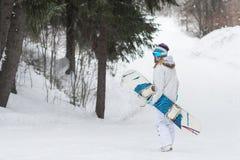 Żeński snowboarder chodzący z snowboard w zimnej zimy pogodzie daleko od Obraz Royalty Free