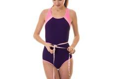 Żeński sporta schudnięcia ciało w simsuit talii z taśmą odizolowywającą na białym tle miarze zdjęcie stock