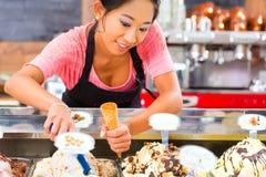 Żeński sprzedawca w bawialni z lody rożkiem Zdjęcia Royalty Free